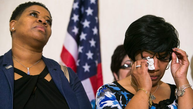 Saundra Floyd, the widow of slain Lt. Steven Floyd Sr., wipes tears from her eyes as her attorney announces the filing of a federal lawsuit against former Govs. Jack Markell and Ruth Ann Minner and others seeking compensatory and punitive damages.