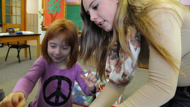 Volunteer Hanna Mallien of Sturgeon Bay helps Ruby Knaup of Forestville wrap presents she selected for her family last year at the Children's Christmas Store at St. Joseph Parish in Sturgeon Bay.