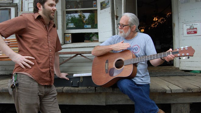 Don Clare, of Rabbit Hash, sits on the old Rabbit Hash General Store porch and strums the guitar that Brad Meinerding, of Covington, repaired for him.