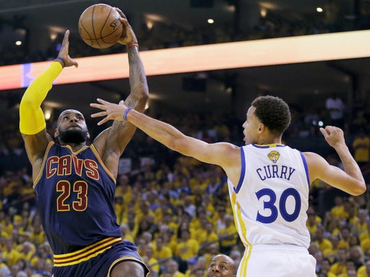 Cleveland Cavaliers forward LeBron James (23) shoots against Golden State Warriors guard Stephen Curry (30) during the first half of Game 5 of basketball's NBA Finals in Oakland, Calif., Sunday, June 14, 2015. (AP Photo/Ben Margot)