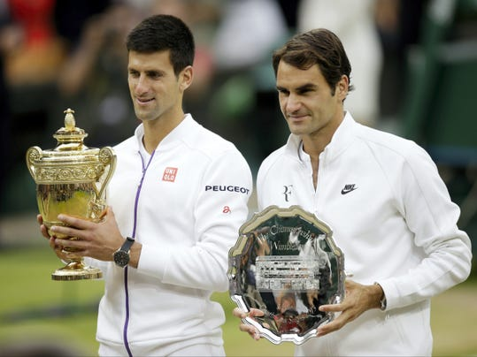 Novak Djokovic, left, and Roger Federer of Switzerland hold their trophies after Djokovic won the men's singles final at the All England Lawn Tennis Championships in Wimbledon, London, on Sunday. Djokovic won the match 7-6, 6-7, 6-4, 6-3.