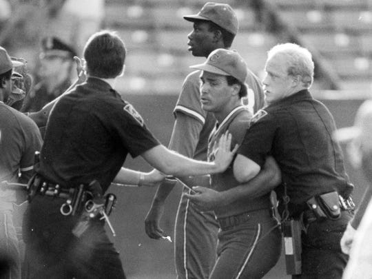 Police restrain a Cuban player after a shouting match