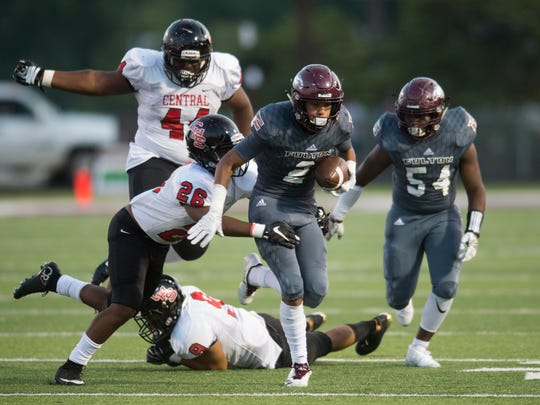 Fulton's Coryean Davis (2) runs with the ball as Central's Malik Robinson (26) tackles him from the side during a high school football game at Fulton against Central Friday, Aug. 25, 2017.