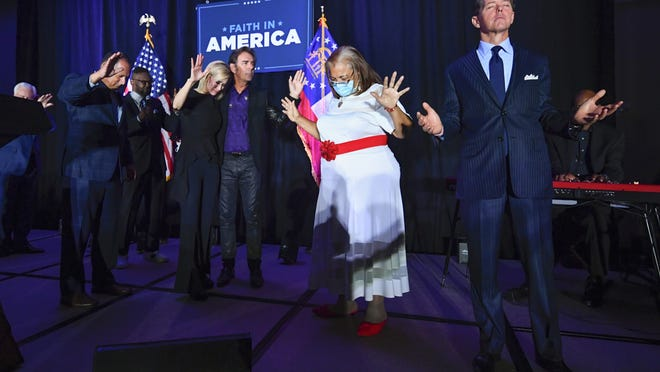 "In this July 23 file photo, from right, Faith & Freedom Coalition founder Ralph Reed, Dr. Alveda King, Journey keyboardist Jonathan Cain, and White House faith adviser Paula White-Cain, and others pray on stage during an Evangelicals for Trump campaign event titled ""Praise, Prayer and Patriotism"" in Alpharetta, Ga."