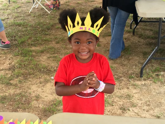 Mia Douglas, 3, wears her new hand-made crown at the Celebrating Brownsville Arts and Cultural Festival Saturday.