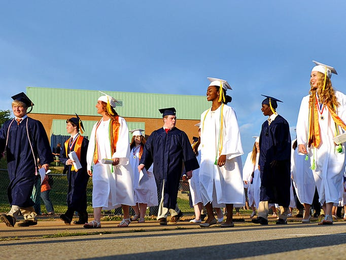 The 2014 class officers, medalists, valedictorian, salutatorian and senior class enter the Dickson County High football stadium Friday.