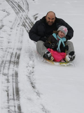John White sleds with his daughter Laney White in Arden