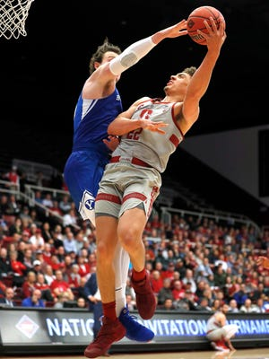 Stanford forward Reid Travis (22) takes a shot over BYU forward Payton Dastrup (15) during the first half of an NCAA college basketball game in the first round of the NIT on Wednesday, March 14, 2018, in Stanford, Calif. (AP Photo/Tony Avelar)