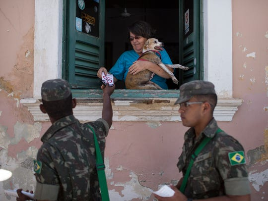 Brazilian Army soldiers distribute flyers with information