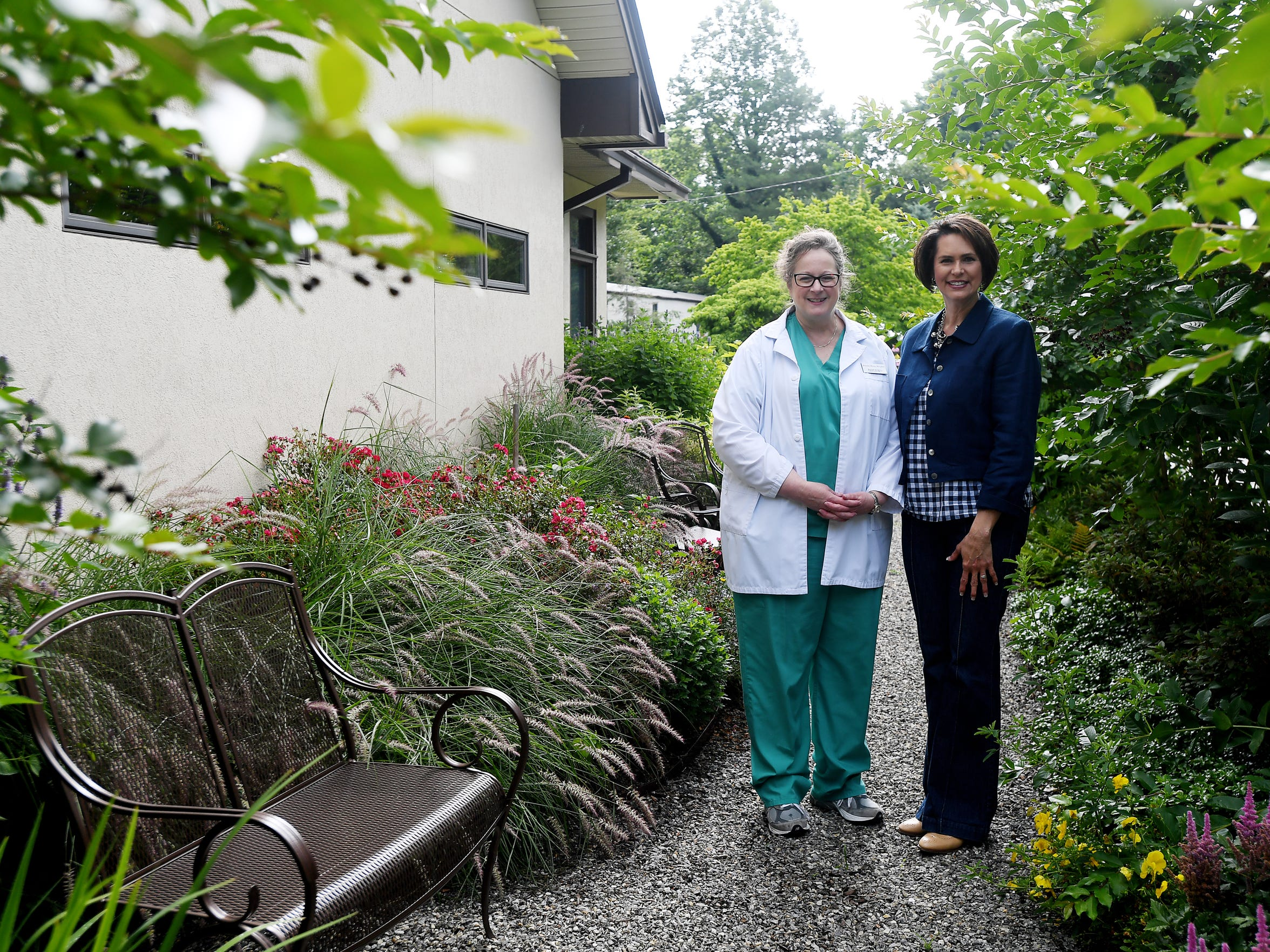 Brenda Mires, a registered nurse and director of clinical services, left, and Debbie Hrncir, a member of the Mountain Area Pregnancy Services board, in the facility's prayer garden on June 14.