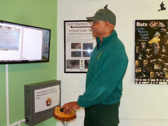 Customer Service Representative George Garnett demonstrates the caving experience available on computer at the Smokey Bear Ranger District office for young and old interested in remotely exploring Fort Stanton Cave.