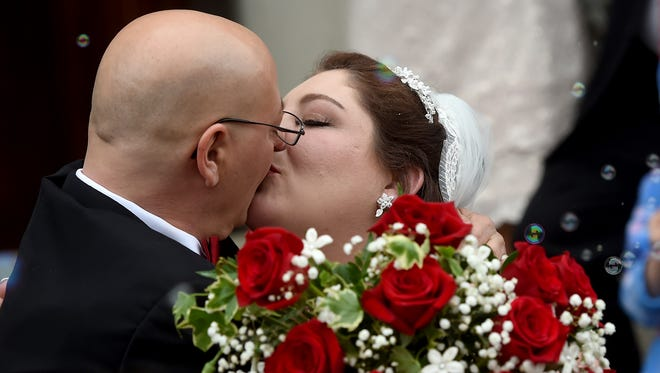 """""""He might leave this earth. He might leave me for now. But I'll see him again someday"""" said Penny Trout, talking about her husband, Adam, as the duo share a kiss outside of St. Paul's United Methodist Church on Saturday.  The newly married couple pushed up their wedding plans when he was diagnosed with pancreatic cancer and given eight months to live."""