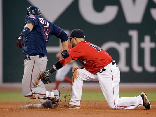 Boston Red Sox second baseman Dustin Pedroia, right, tags out Minnesota Twins's Brian Dozier trying to stretch a single into a double during the fourth inning of a baseball game at Fenway Park, Friday, July 22, 2016, in Boston. (AP Photo/Elise Amendola)