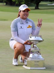 Inbee Park holds up three fingers and poses with the trophy after winning the KPMG Women's PGA Championship at the Westchester Country Club in Harrison, June 14, 2015. This is the third year in a row that she won the event.