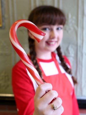Kiera Bertrand, 18, holds a candy cane made the old-fashioned way at Lucas Candies in Haverstraw Dec. 6, 2016. Lucas Candies is celebrating its 120th anniversary with candy cane demonstrations during the Christmas season.