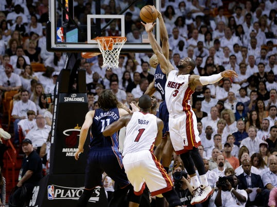 Miami Heat's Dwyane Wade (3) shoots over Charlotte Bobcats' Gerald Henderson, second from right, during the second half in Game 1 of an opening-round NBA basketball playoff series on Sunday, April 20, 2014, in Miami. The Heat defeated the Bobcats 99-88. (AP Photo/Lynne Sladky)