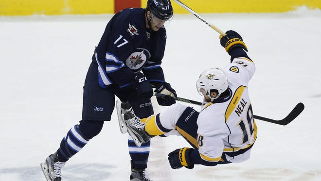 The Jets' Adam Lowry (17) levels the Predators' James Neal (18) in the first period Thursday.