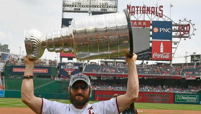 Washington Capitals forward Alex Ovechkin lifts the Stanley Cup at the Nationals' game Saturday.