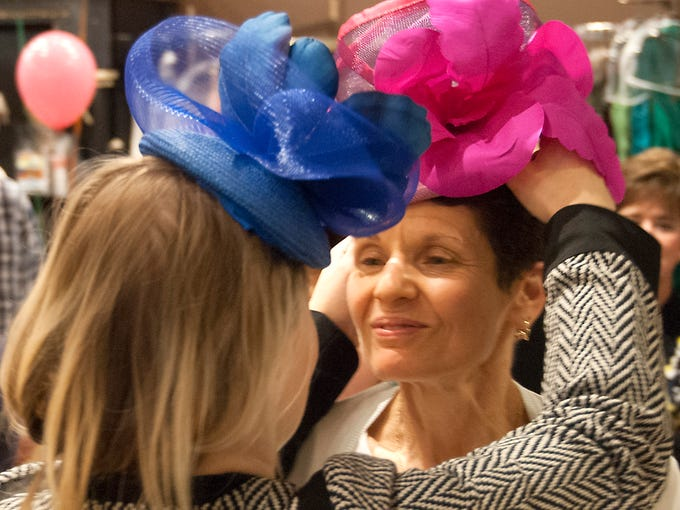 Paulette Dubofsky is helped by Jenny Pfanenstiel with a hat made by Pfanenstiel during a HerScene fashion event at Rodeo Drive boutique.