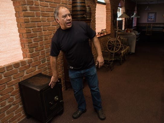 Marti'n Sanchez stands next to an antique safe at Old West Steakhouse on Beaglin Park Drive on Tuesday.