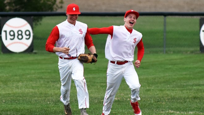 Brady Turnes, left, is congratulated by center fielder Logan Farmer after making a diving catch in left field that secured Sheridan's 5-3 win against visiting Philo on Wednesday.