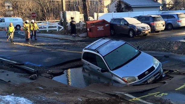 Ramapo police said the driver of this car ignored road barriers before ending up in this hole were crews were fixing a water main break on Saddle River Road on Feb. 13, 2016.