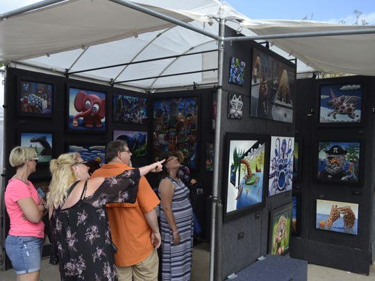 Artstreet attendees check out the artwork by Green Bay artist Melvin McGee at his booth on Cherry Street during the 35th annual festival Sunday, Aug. 28, 2016.