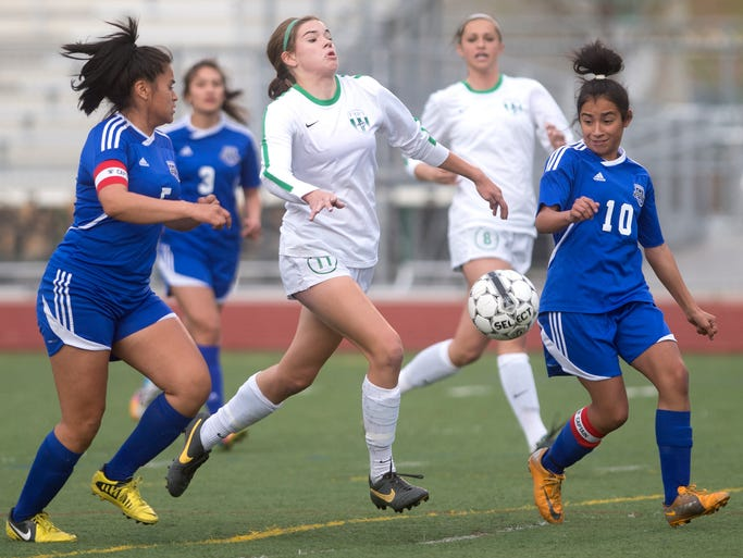Fossil's Grace Cutler, center, races between Hinkley's Kimberly Fuentes, left, and Diana Rivera during a first-round playoff game at Fossil Ridge High School in Fort Collins Tuesday, May 6, 2014. Fossil Ridge topped Hinkley 10-0 and will face Doherty on Friday.