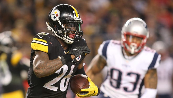 Pittsburgh Steelers running back Le'Veon Bell (26) rushes the ball as New England Patriots defensive end Jabaal Sheard (93) chases during the fourth quarter at Heinz Field.