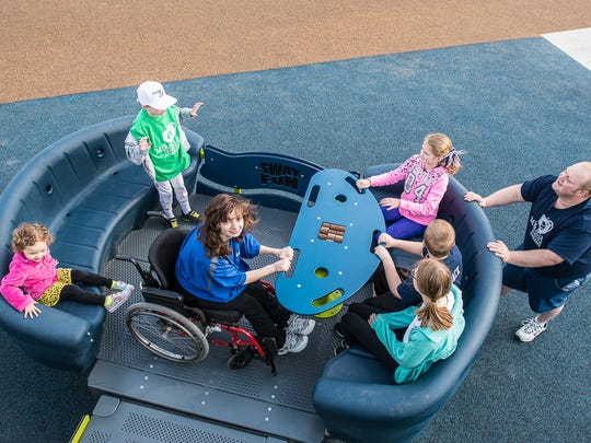 Children play on a wheelchair accessible playground at Ankeny's Miracle Park, 300 Northwest School St.