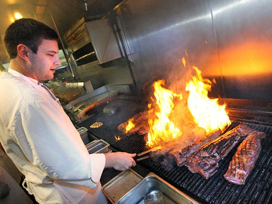Chef Kyle Roberts grills steaks at Harry & Izzy's North, one of 50 restaurants offering three-course, value-priced steak menus during Devour Indy.