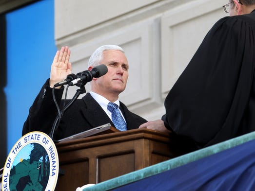 Indiana Supreme Court Chief Justice Brent E. Dickson, right, administers the oath of office to Gov. Mike Pence during the inauguration ceremony on the west steps of the Statehouse on Monday, Jan. 14, 2013.