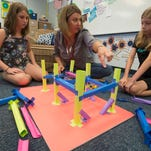 Fifth-grade teacher, Erin Tracy, center, gives Avi Mayhew, left, and Olivia Smith, right, a little guidance on building a paper roller coaster during class at Oriole Beach Elementary School Friday morning. The two fifth-grade girls are in Tracy's ACES class, Academic, and Creative Enrichment for Students.