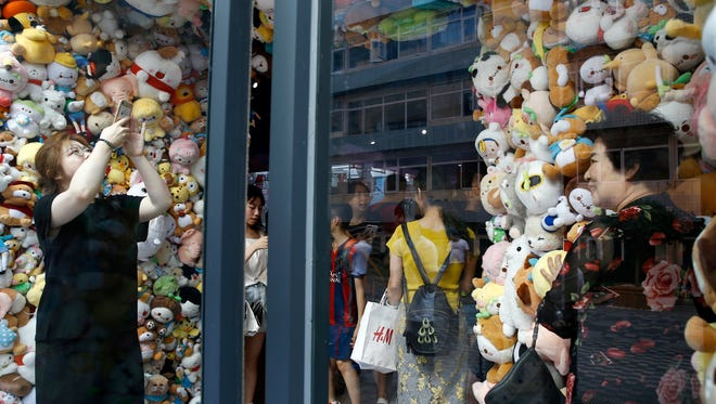 In this Sunday, July 15, 2018, photo, women take souvenir photos with soft toys on display at an arcade games shop in Beijing. China's economic growth slowed in the quarter ending in June, adding to challenges for Beijing amid a mounting tariff battle with Washington.