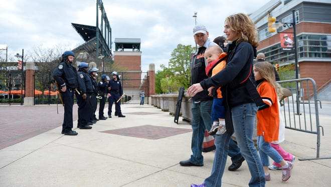 Baseball fans make their way towards Oriole Park at Camden Yards as Baltimore police stand watch Monday.
