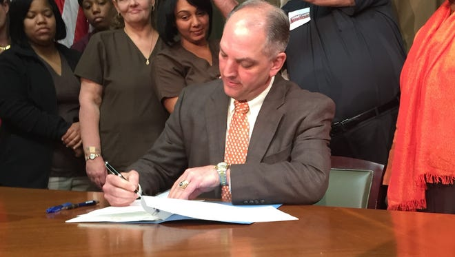 Gov. John Bel Edwards signs an executive order Tuesday to expand Medicaid.