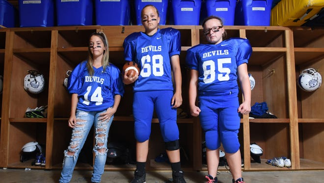 Three girls are playing football for Zanesville Middle School.