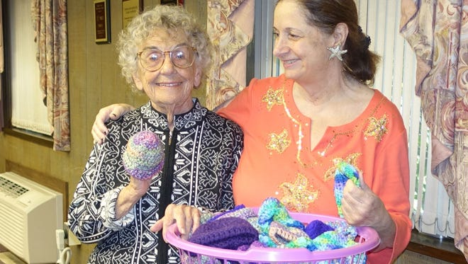 Josephine Pagano (left) and Eva Prestopino, members of the Woman's Club of Vineland, show off some of the purple hats for newborns club members have made to donate to support the state project which is prevention of child abuse. Prestopino is the club's coordinator for the project.