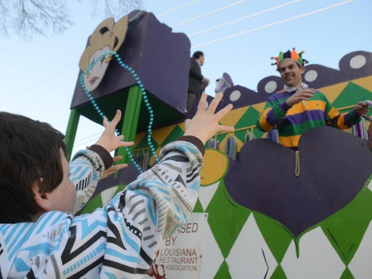 A child catches beads from a passing float at the 2015