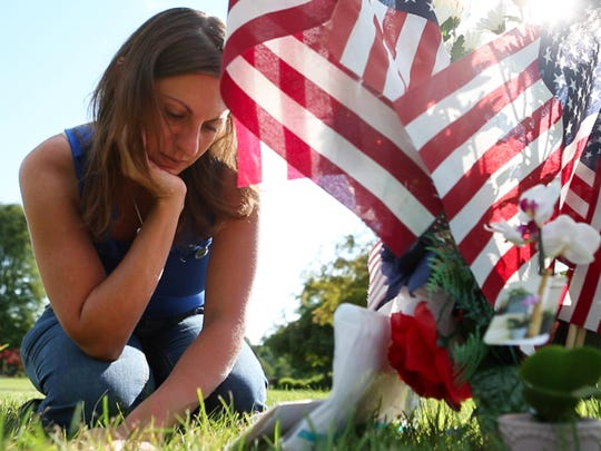 Amy Pierson sits at Daryl's Pierson's grave following the sentencing of Thomas Johnson III on Thursday, July 16, 2015.