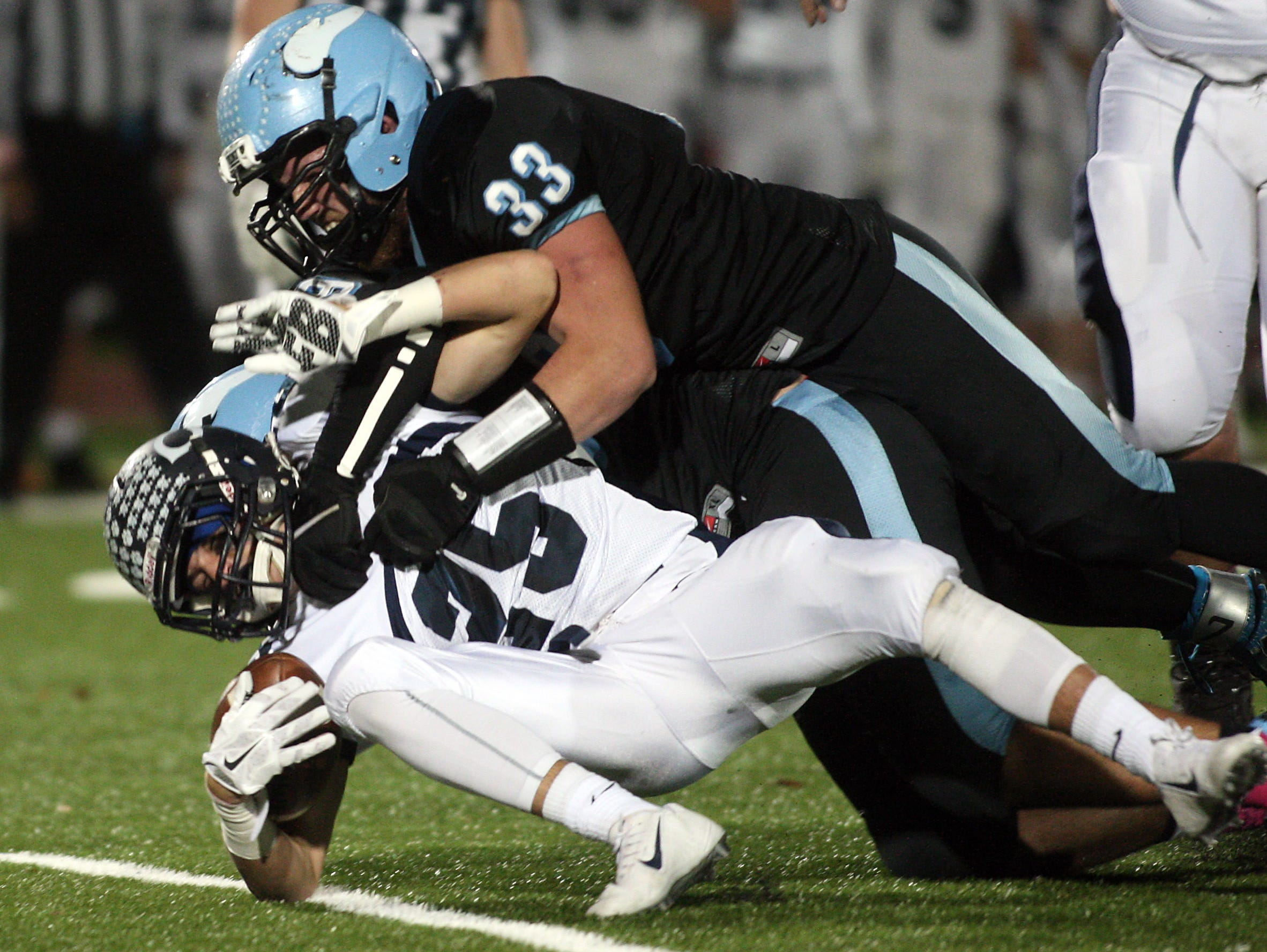 Chatham running back Timmy Adams taken down by Parsippany Hills Jared Salgado (33) and Russell Hohn in a showdown with playoff implications. October 30, 2015, Parsippany, NJ.