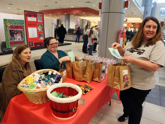Crystal DiLuzio (right) leads a distribution of gift bags of basic supplies and goodies to truckers in honor of her late husband along with friends Jen Stein (left) and Tara LeGates at the Delaware Welcome Center Saturday.