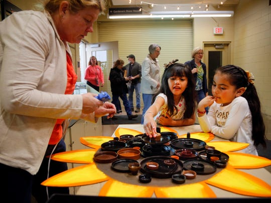 Children use plastic bottle caps to make a sunflower at the Greater Des Moines Botanical Garden during the downtown Earth Day tour in April 2018.