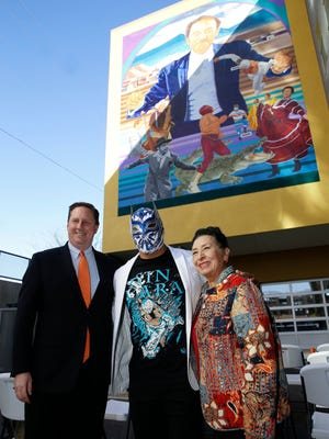 """Joe Gudenrath, executive director of the Downtown Management District, stands with WWE wrestling superstar Sin Cara and educator and International Folklorico Dance Group founder Rosa Guerrero, at the March unveiling of the  """"Latino Icons"""" mural at the Roderick Artspace Lofts in Downtown El Paso."""