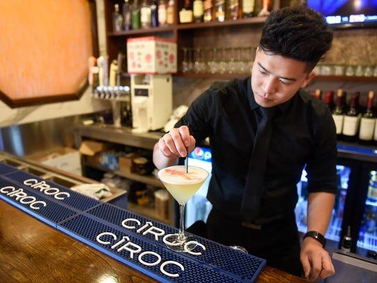 Co-owner Michael Nguyen mixes a signature cocktail