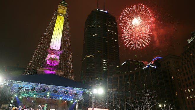 "The ""tree"" is lit and fireworks begin during Downtown Indy's 54th annual Circle of Lights, presented by Contractors of Quality Connection and Electrical Workers of IBEW #481 on Monument Circle, Indianapolis, Friday, Nov. 25, 2016. Their grandmother Helen Williams watches from behind."