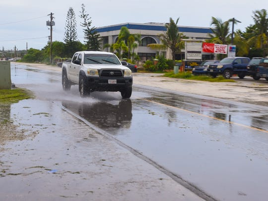 A motorist splashes through a puddle of standing water along Finegayan Road, commonly called Hamburger Road, in Harmon in Friday, Aug. 18, 2017.