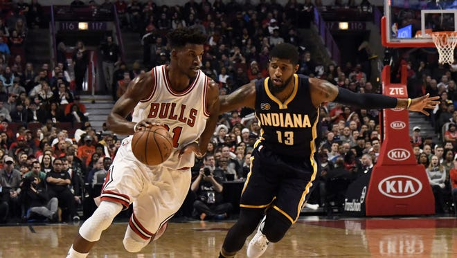 Dec 26, 2016; Chicago, IL, USA; Chicago Bulls forward Jimmy Butler (21) is defended by Indiana Pacers forward Paul George (13) during the first half at the United Center. Mandatory Credit: David Banks-USA TODAY Sports