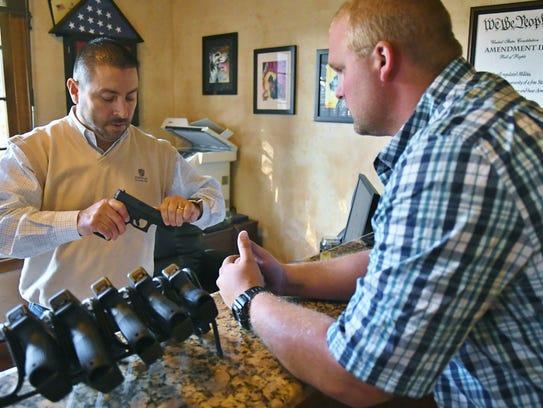 Scott James shows Mitchel Tenhet handguns on Monday,