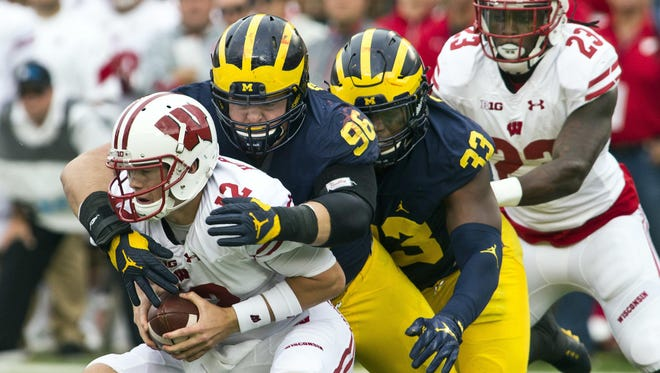Michigan's Ryan Glasgow, middle, along with Taco Charlton, sack Wisconsin quarterback Alex Hornibrook on Oct. 1 in Ann Arbor.
